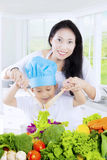 Child and mother stirring salad. Male child and her mother making and stirring a bowl of vegetables salad in the kitchen Stock Photos