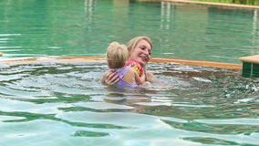 Child and mother swim in the pool stock video footage