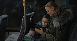Child and mother traveling by bus and looking at photos in cellphone stock video