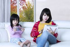 Child and mother use gadgets Stock Photo