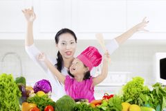 Child and mother with vegetables. Little girl and her mother raising hands in the kitchen with fresh vegetables on the table, shot at home royalty free stock photography