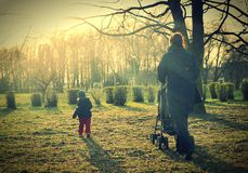 Child with mother walking in sunlight. Royalty Free Stock Photos