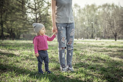 Child with mother walking together with holding hands in summer park on grass. Main subject is child. Royalty Free Stock Photography