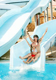 Child with mother on water slide at aquapark. Stock Images