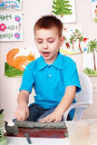 Child  mould from clay in play room. Stock Photo