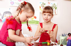 Child mould  plasticine in playroom. Royalty Free Stock Photo