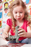 Child  moulding from clay in play room. Royalty Free Stock Images