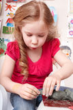Child moulding from clay in play room. Stock Image