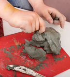 Child moulding from clay in play room. Royalty Free Stock Image