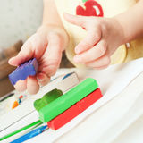 Child moulds from plasticine on table, hands with plasticine. Baby girl playing with color play plasticine Stock Images