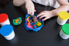 Child moulds from plasticine on table, hands with plasticine Royalty Free Stock Photography