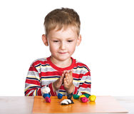 Child moulds toys from plasticine Royalty Free Stock Photos