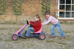 Child moves pedal car. Twins playing with a pedal car go cart Stock Photos