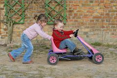 Child moves pedal car. Twins playing with a pedal car go cart Royalty Free Stock Photos