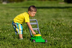 Child mowing grass Stock Photo