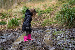 Child in mud on track through woodland Royalty Free Stock Photos