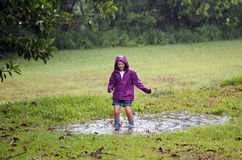 Child in muddy puddle. Teen child happily jumping in a muddy puddle on a fun rainy day stock photo