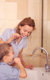 Child with mum cleaning teeth in bathroom Royalty Free Stock Photo