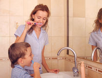 Child with mum clean a teeth in bathroom. 2 stock photo