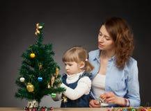 Child with mummy decorates the Christmas tree Stock Photos