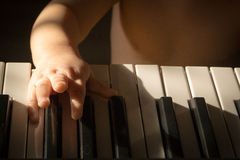 Child and music. Baby trying to play the keyboard Royalty Free Stock Image
