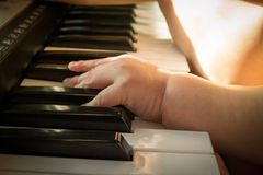 Child and music. Baby trying to play the keyboard Stock Photo