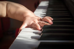 Child and music. Baby trying to play the keyboard Royalty Free Stock Photos