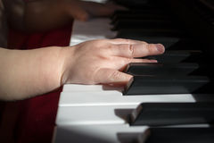 Child and music. Baby trying to play the keyboard Stock Images