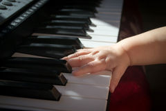 Child and music. Baby trying to play the keyboard Royalty Free Stock Photo