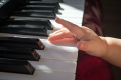 Child and music. Baby trying to play the keyboard Royalty Free Stock Photography
