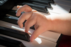 Child and music. Baby trying to play the keyboard Stock Image