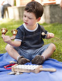 Child with musical instruments. Portrait of a toddler child,  sitting in a garden and playing with a musical instruments - bells and xylophone Stock Photo