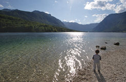 Child and Nature. Small child standing near the lake Stock Images