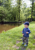 Child in nature park. Small child walking on a grass path along a river or a canal in a park or in nature Stock Images