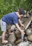 Child at nature water stream. Child washing hands in water stream with wooden fountain Stock Photography