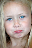 Child naughty. A beautiful little caucasian white girl child head portrait with bright blue eyes, long blond hair and naughty funny expression in her pretty face Royalty Free Stock Photography