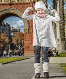 Child near Arc de Triomf in Barcelona, Spain showing strength. In Barcelona for a perfect winter. Full length portrait of happy trendy child near Arc de Triomf Stock Image