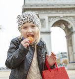 Child near Arc de Triomphe eating French macaroon Stock Photo