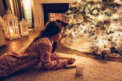 Child near Christmas tree stock images