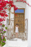 A child near an old door with stairs and flowers Stock Photo