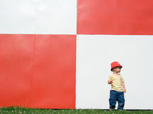 Child Near Red and White Wall Stock Images