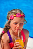 Child near swimming pool is drinking cold squeezed orange juice. Stock Images