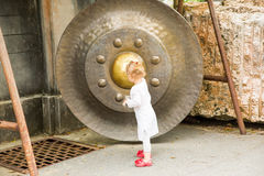 Child near Thai gong in Phuket. Tradition asian bell in Buddhism temple in Thailand. Famous Big bell wish near Gold Buddha Royalty Free Stock Photography