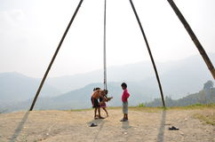 Child nepalese playing swing machine made for bamb. Oo at outdoor of countryside Pokhara in Annapurna Valley Nepal Stock Photos