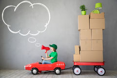 Child New Home Moving Day House Concept. Happy child playing into new home. Kid having fun indoor. Moving house day and express delivery concept Royalty Free Stock Image