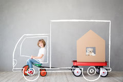 Child New Home Moving Day House Concept. Happy child playing into new home. Kid having fun indoor. Moving house day and express delivery concept Stock Photo
