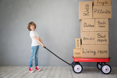 Child New Home Moving Day House Concept. Happy child playing into new home. Kid having fun indoor. Moving house day and express delivery concept Royalty Free Stock Photo