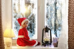 A child in the new year looks out the window. Children are waiti. Ng for Santa Claus. A child in Santa suit sits at the window.r stock photography