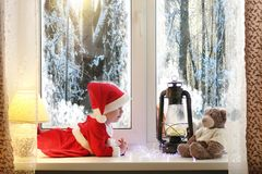 A child in the new year looks out the window. Children are waiti. Ng for Santa Claus. A child in Santa suit sits at the window.r stock images
