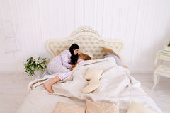 Child not listen but Couple trying to sleep, lying on bed in whi Stock Photography